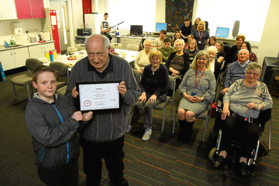 Picture shows pupil Declan Knapp and resident Henry Carrie, holding the award, with some of the Corso Street residents, staff and pupils at Harris.