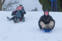 Eleven-year-olds Natasha Turnbull and Liam Dick  chase dad Steven Dick down the hill while sledging at Riverside Park, Glenrothes