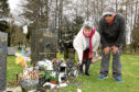 Mother and son, Marion and Christopher Ali, pictured at the graveside which was run over by a council worker on a sit-on lawnmower