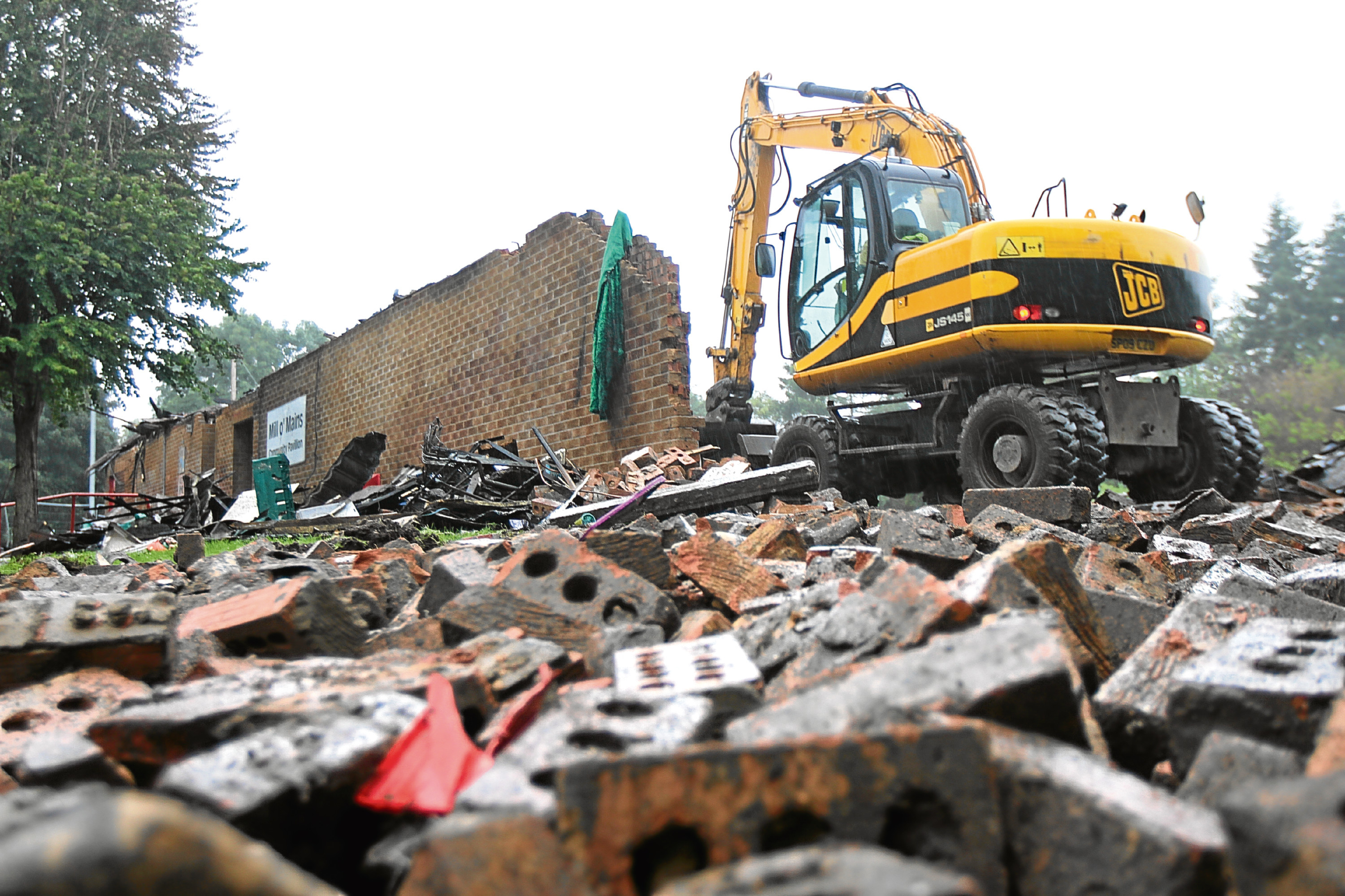 Diggers at work clearing the remains of the former Mill o' Mains Community Pavilion destroyed in a fire last year.