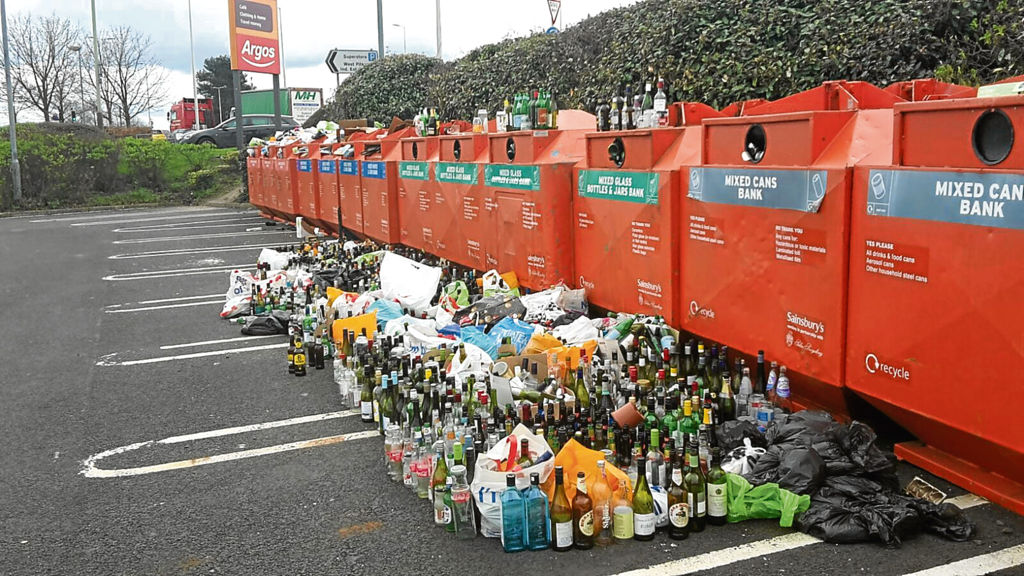 Hundreds of bottles left lying beside the overflowing recycling bins at Sainsbury's.