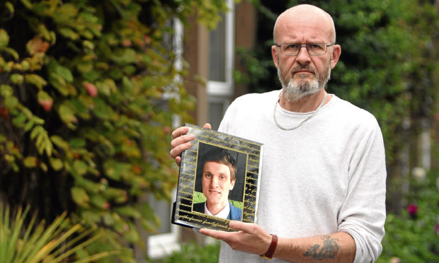 Phil Welsh with a picture of his son.