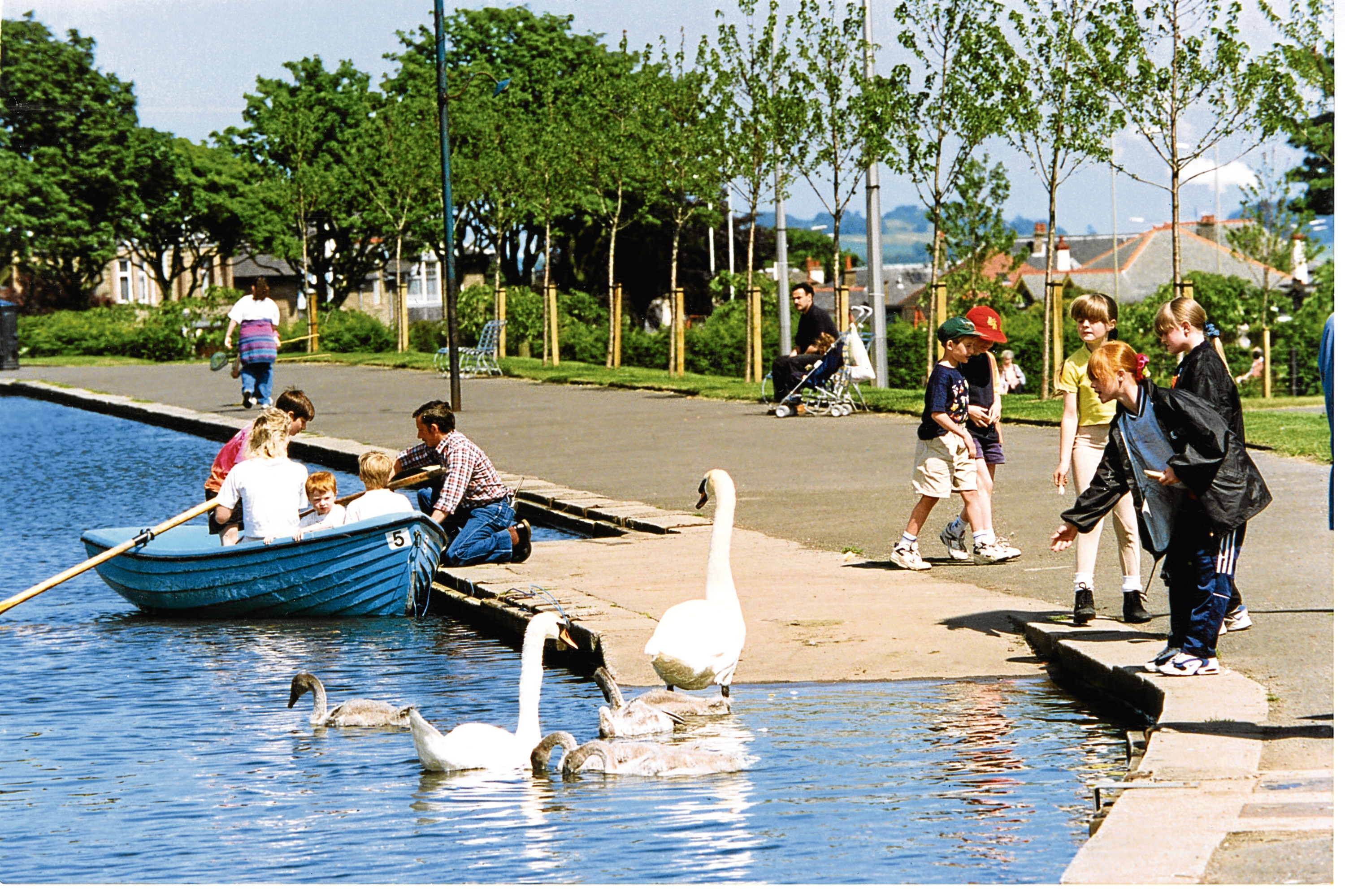 Back in the Day Saturday 28 April  Feeding the Swans. Photograph shows a group of children enjoying the sunny day at Stobsmuir Pond, Dundee, while feeding the bevy of Swans nearby. 8 July 1996. H262 1996-07-08 Feeding the Swans (C)DCT Dundonian. Used in Courier L/ED 9 July 1996.