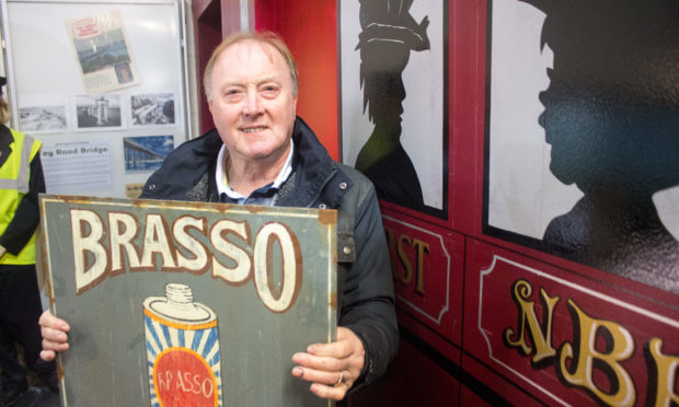 Brian holds one of the signs which he made from scratch, while standing beside the carriage he painted.