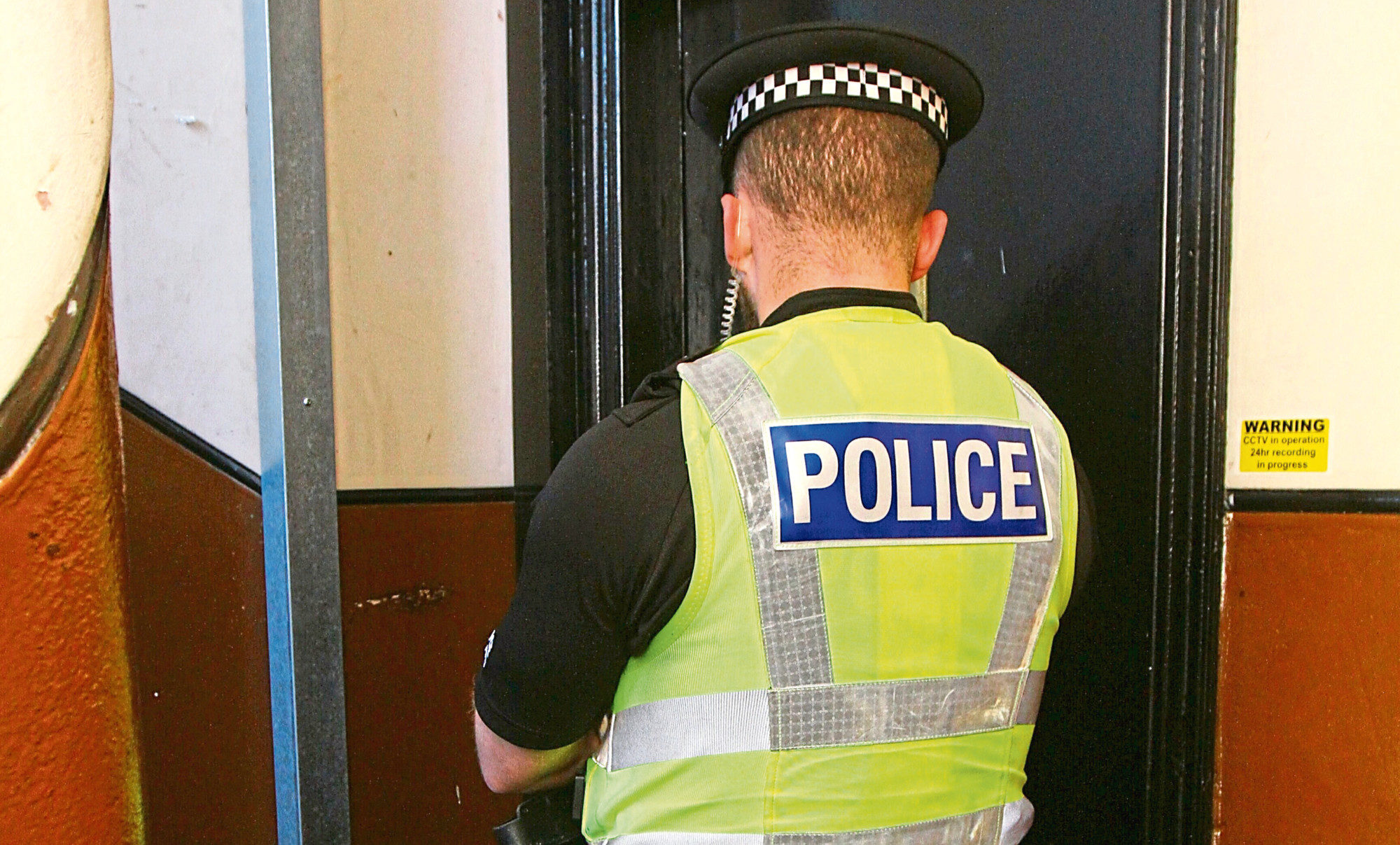 A police officer on duty at the door of the flat in Brown Constable Street