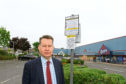 Murdo Fraser beside one of the signs at the retail park