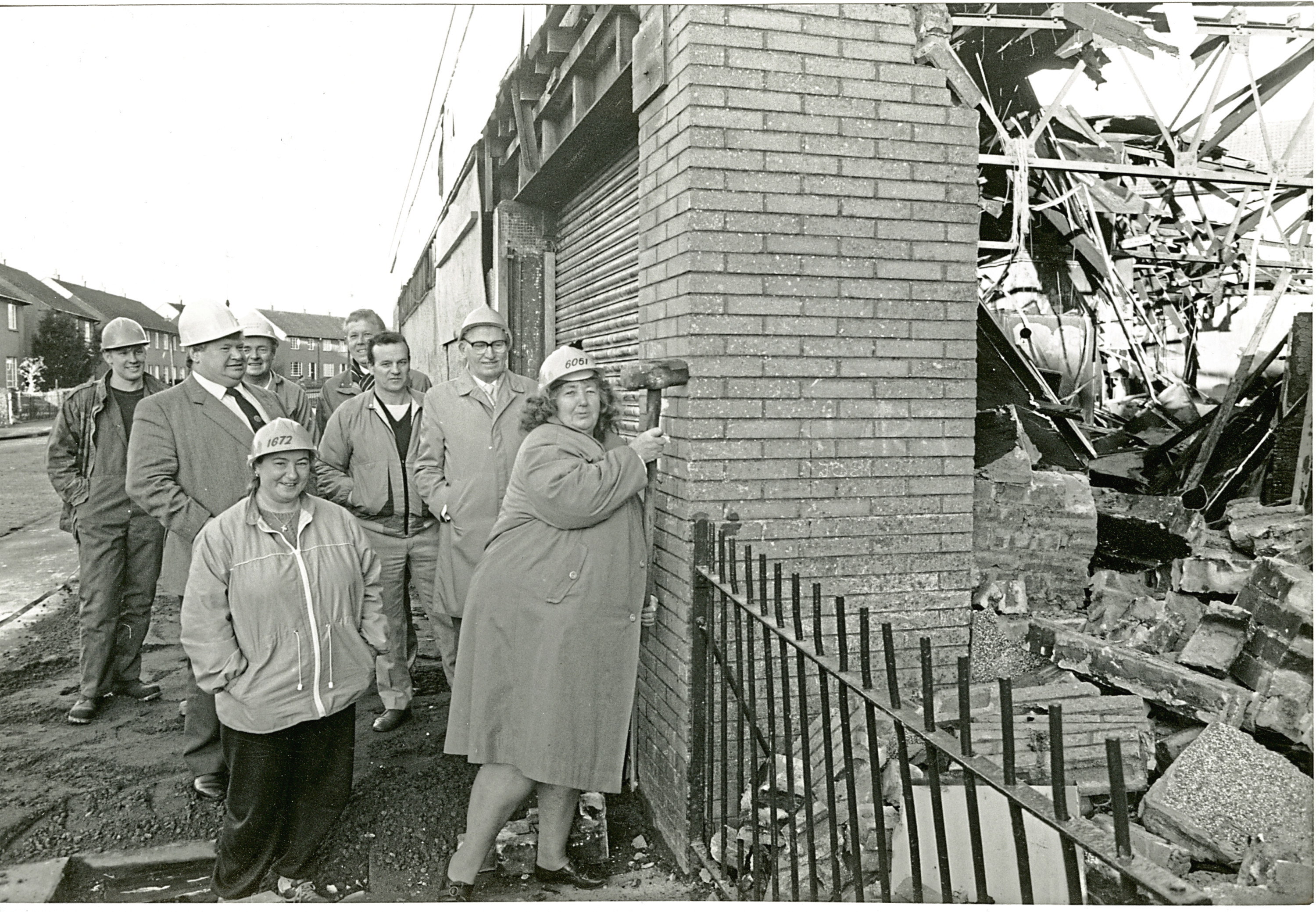 Demolition of Burnt Out Store. The burnt out wreck of a former General Store in Dundee's West March housing scheme was finally demolished two years after it was gutted in a looting spree by local youths. The shops in Balmuir Road was demolished watched by Councillor William McCormack, residents and other officials. 9 January 1989. H259 1989-01-09 Demolition of Burnt Out Store (C)DCT Dundonian. Used in Tele & Post 9 January 1989.