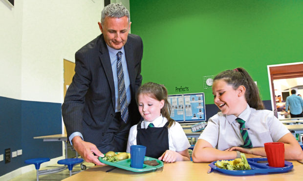 Picture shows Gary Conway, facilities business manager at Tayside Contracts, serving lunch to Martina Lewandowska, left, and Denni Cussick at Rowantree Primary School.