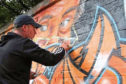Artist Symon Mathieson, who is painting the wall at Thomson Park in Lochee