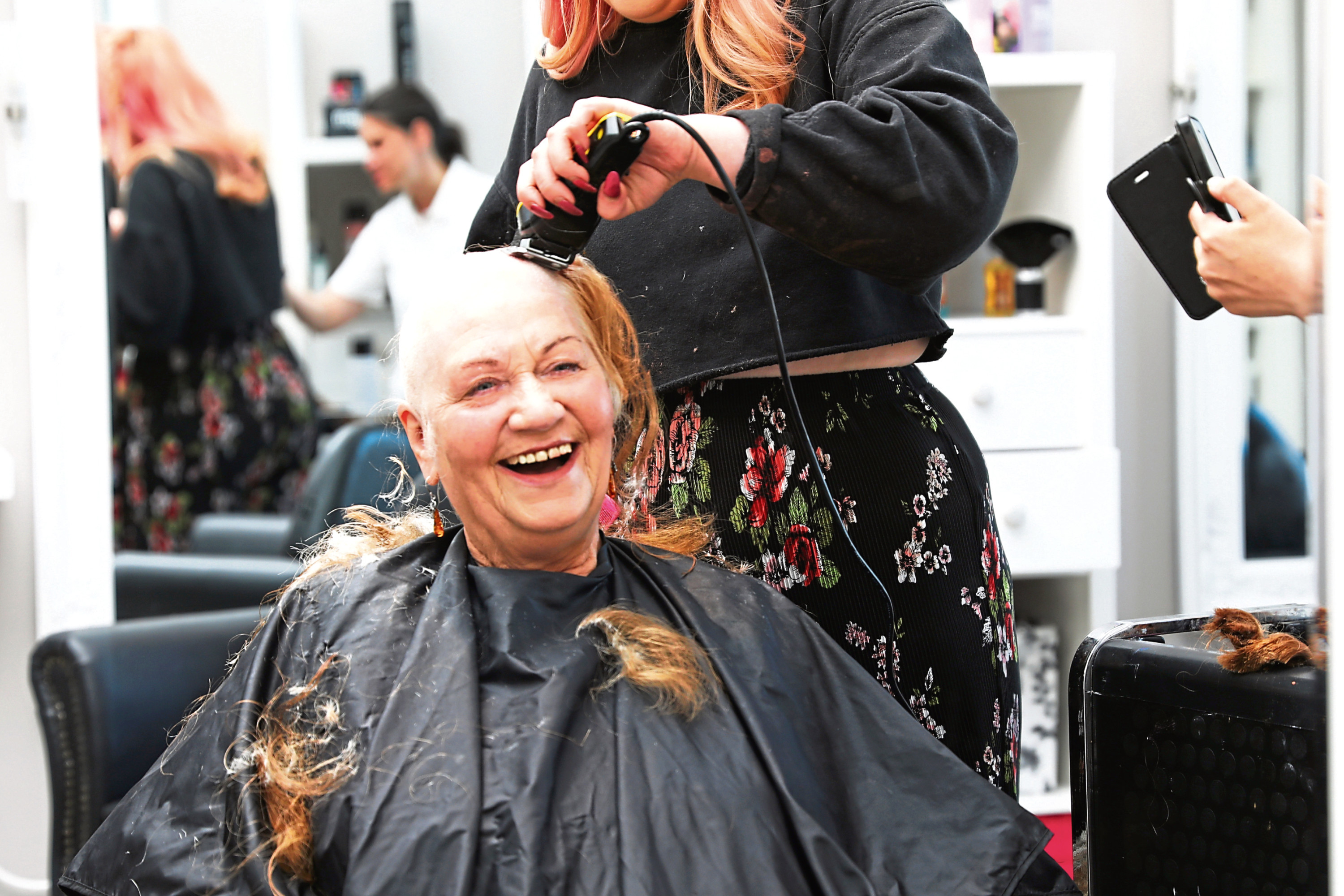 Picture shows Melba smiling as her waist-length hair is shaved off.