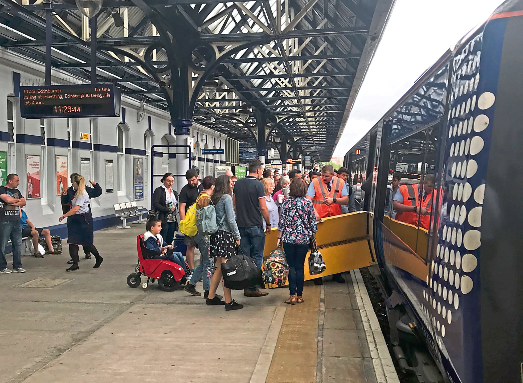Passengers at Dundee station attempt to board another train after their service was terminated.