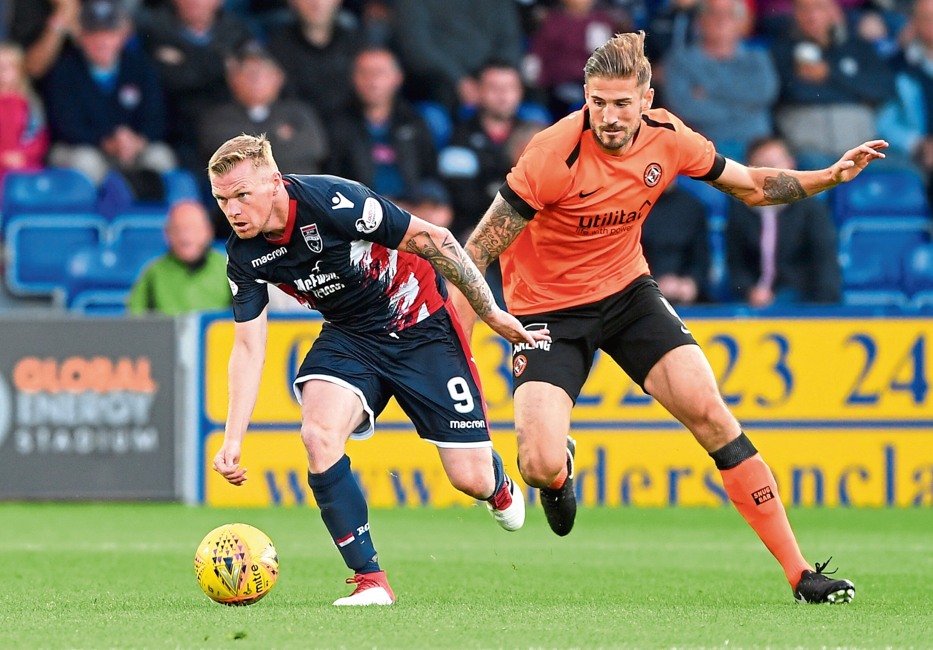 Former Dundee United striker Billy Mckay turns away from Frederic Frans during Tuesday night's game in Dingwall.
