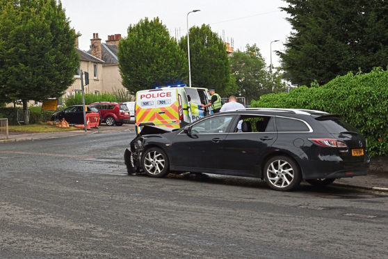 Police at the scene and the damaged Mazda