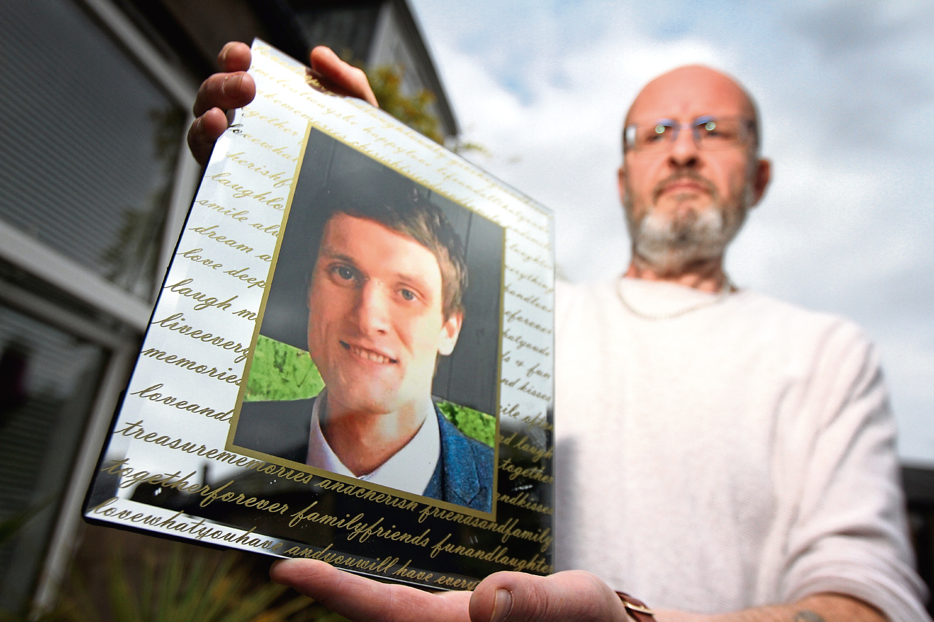 Phil Welsh with a photo of Lee, who took his own life