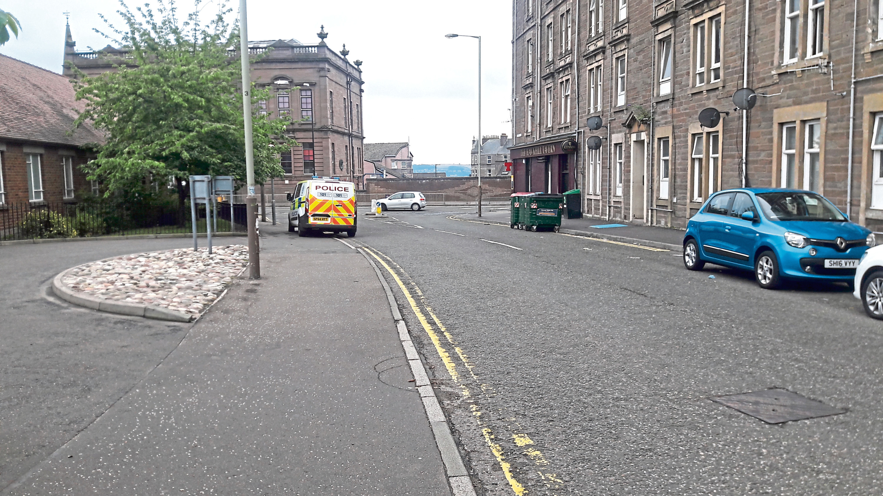The man's body was discovered in a property on Peddie Street, close to the Hawkhill Tavern, seen on the right of the picture across from the police van.