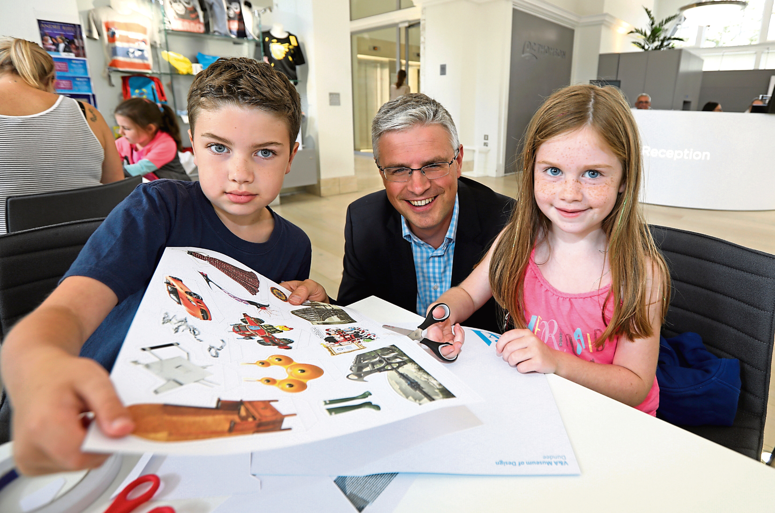 DC Thomson director David Thomson helps nine-year-old Alex and six-year-old Anna Paterson with their pop-up book