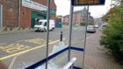 Glass is strewn across the pavement and road at one of the damaged bus shelters.