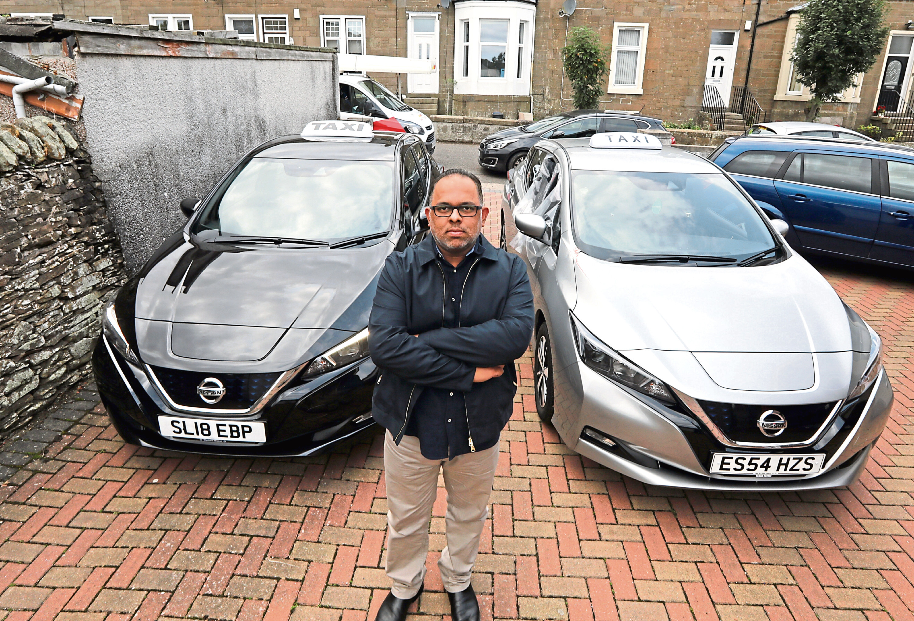 Irfan Nassir with the two vandalised Nissan taxis
