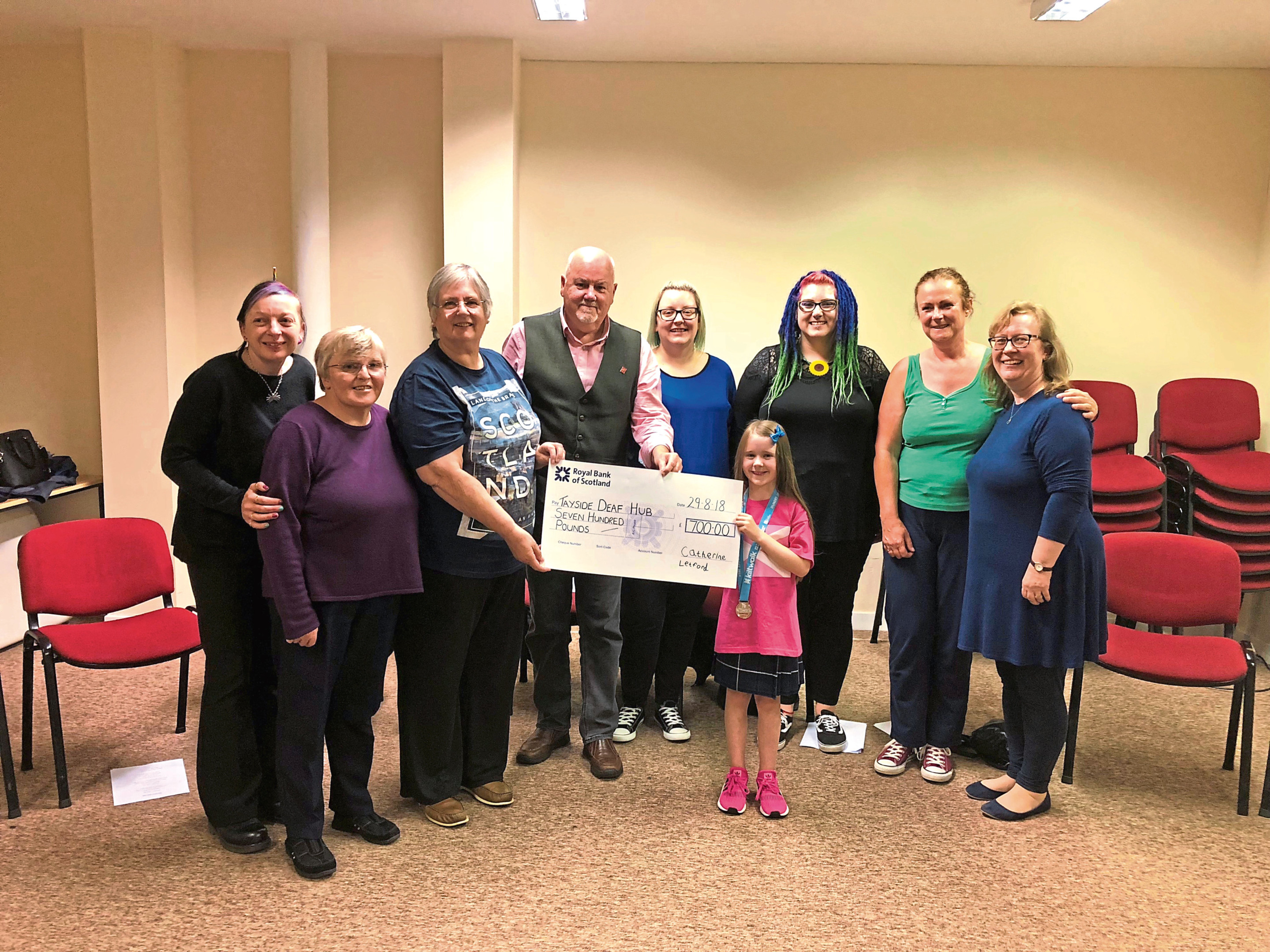 Catherine Letford hands over the cheque after raising £700.