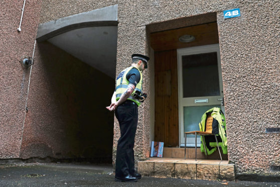 A police officer stands guards the outside of a property on the city's Ladywell Avenue, where a cannabis cultivation was discovered