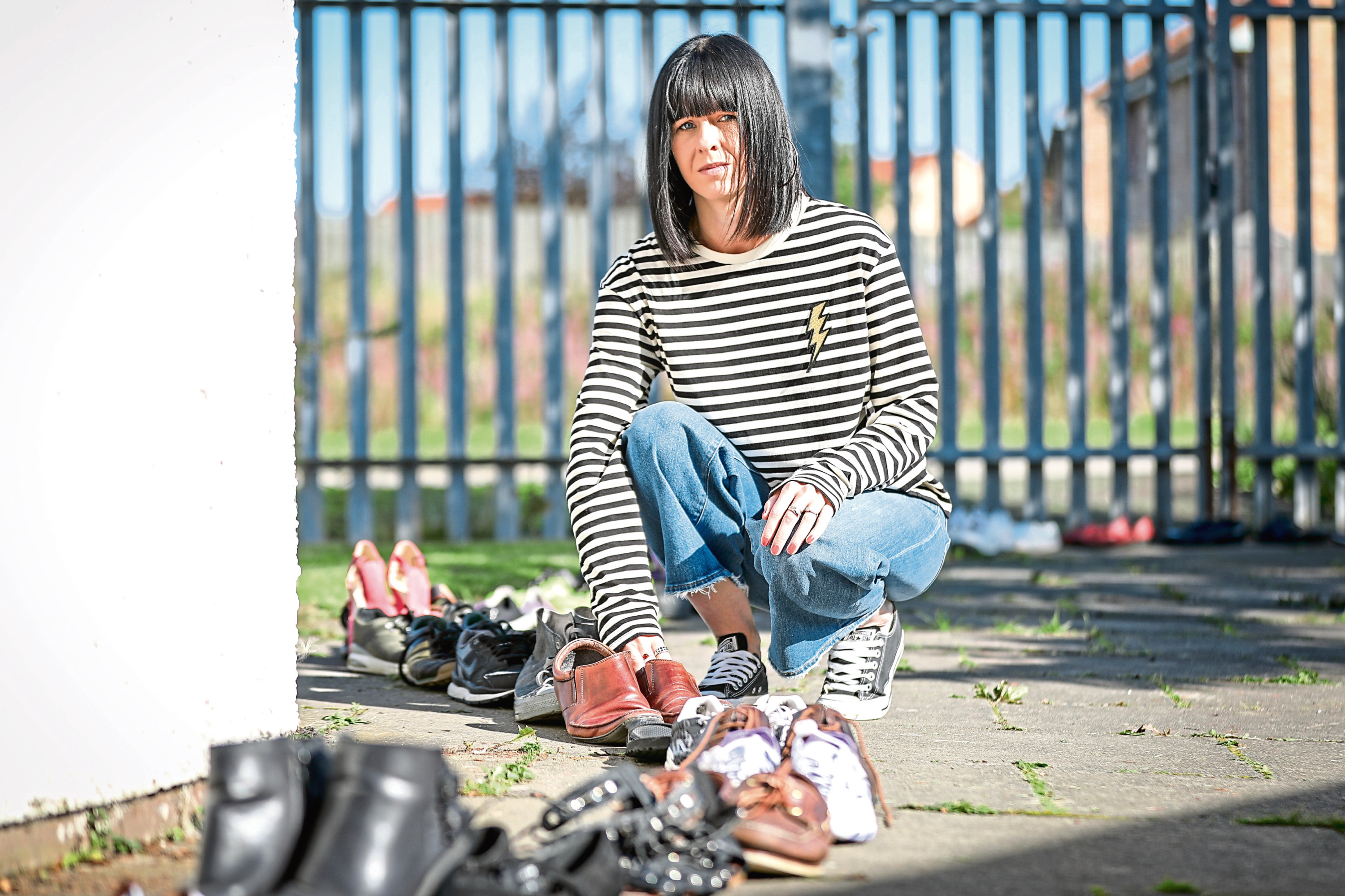 Bobbie Haggart, advanced practitioner at Addaction, with the shoes and cross lined up for the service