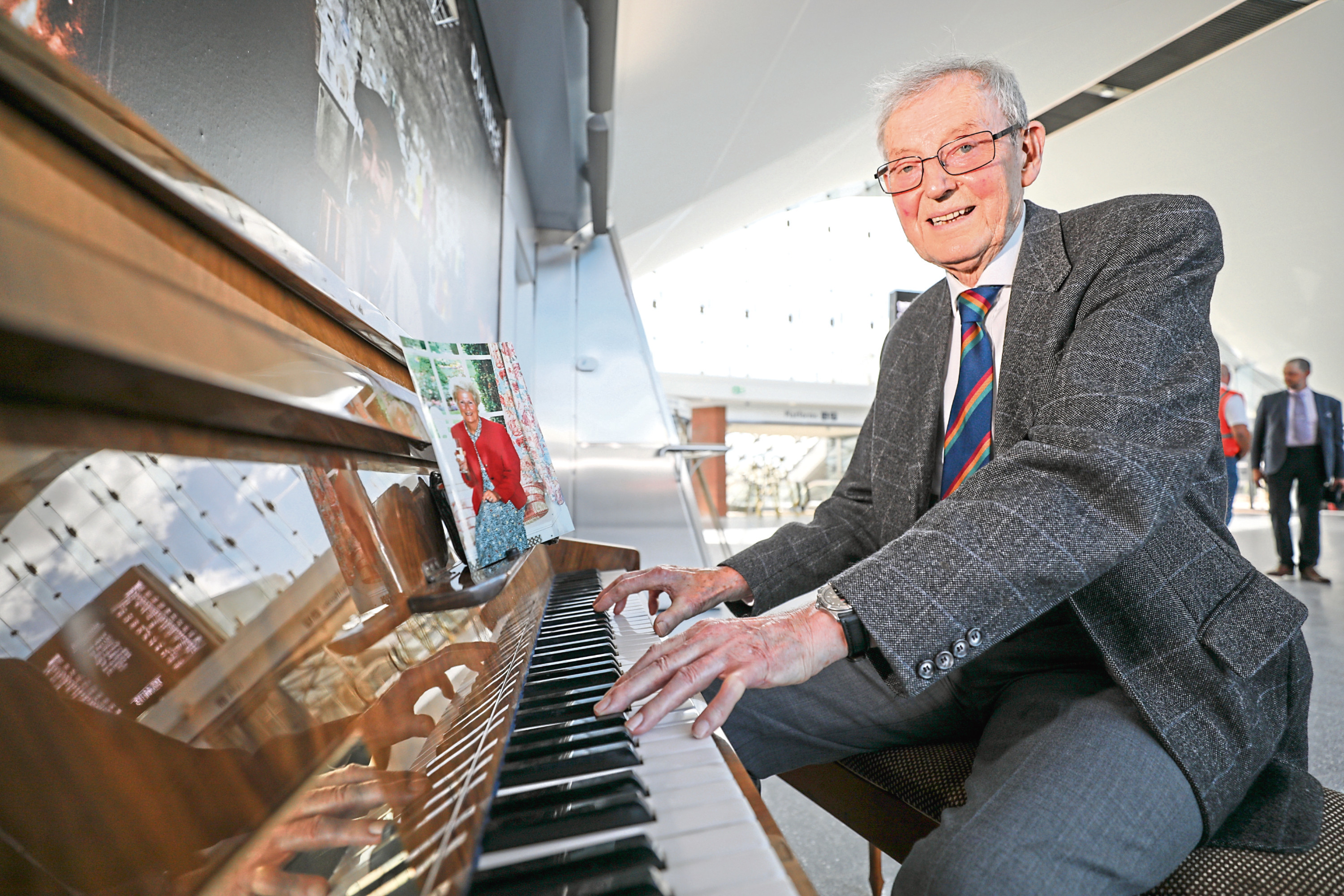 Courier News, Scott Milne story, CR0002422 Dave Patterson has donated a piano to Dundee Railway station in memory of his wife Jean Patterson who worked fro ScotRail for 10 years. PIc shows; Dave Patterson at the piano with a photo of his wife Jean. Sunday, 8th July, 2018.