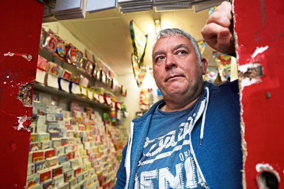 Owner Cliff Robertson at the shop door where the locks were smashed in