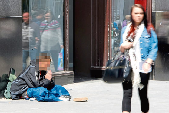 A homeless person outside a shop on Dundee's High Street