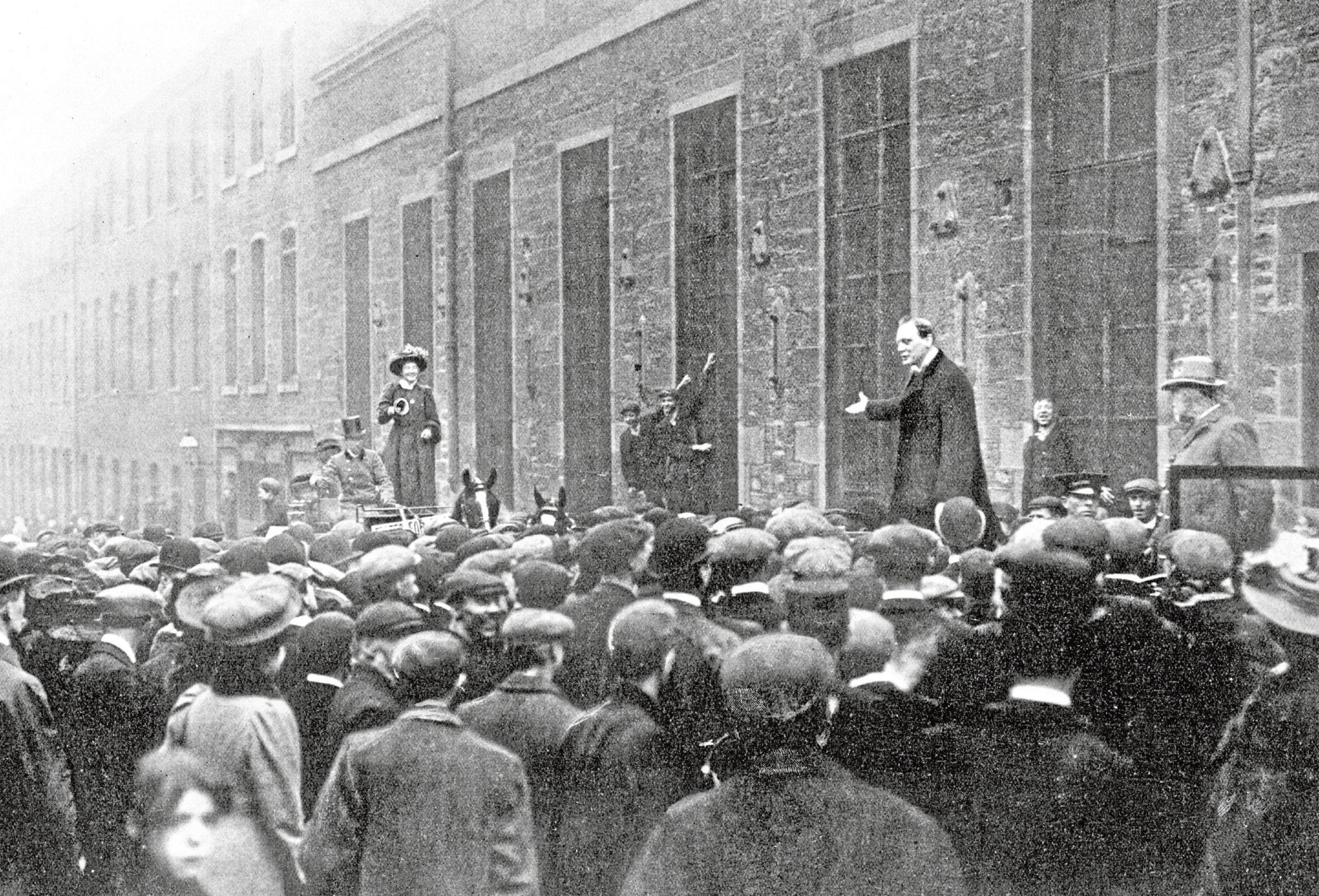 Winston Churchill addresses workmen in the city as Mary Molony arrives to drown out his voice.