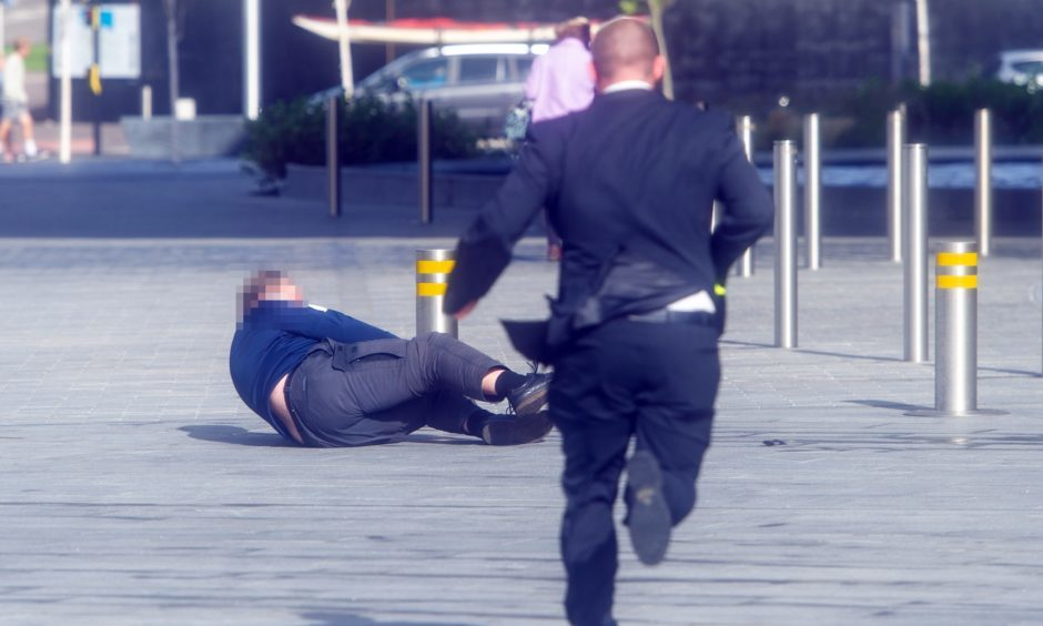 A man rushes to help after another man was swept off his feet by the strong wind outside V&A Dundee