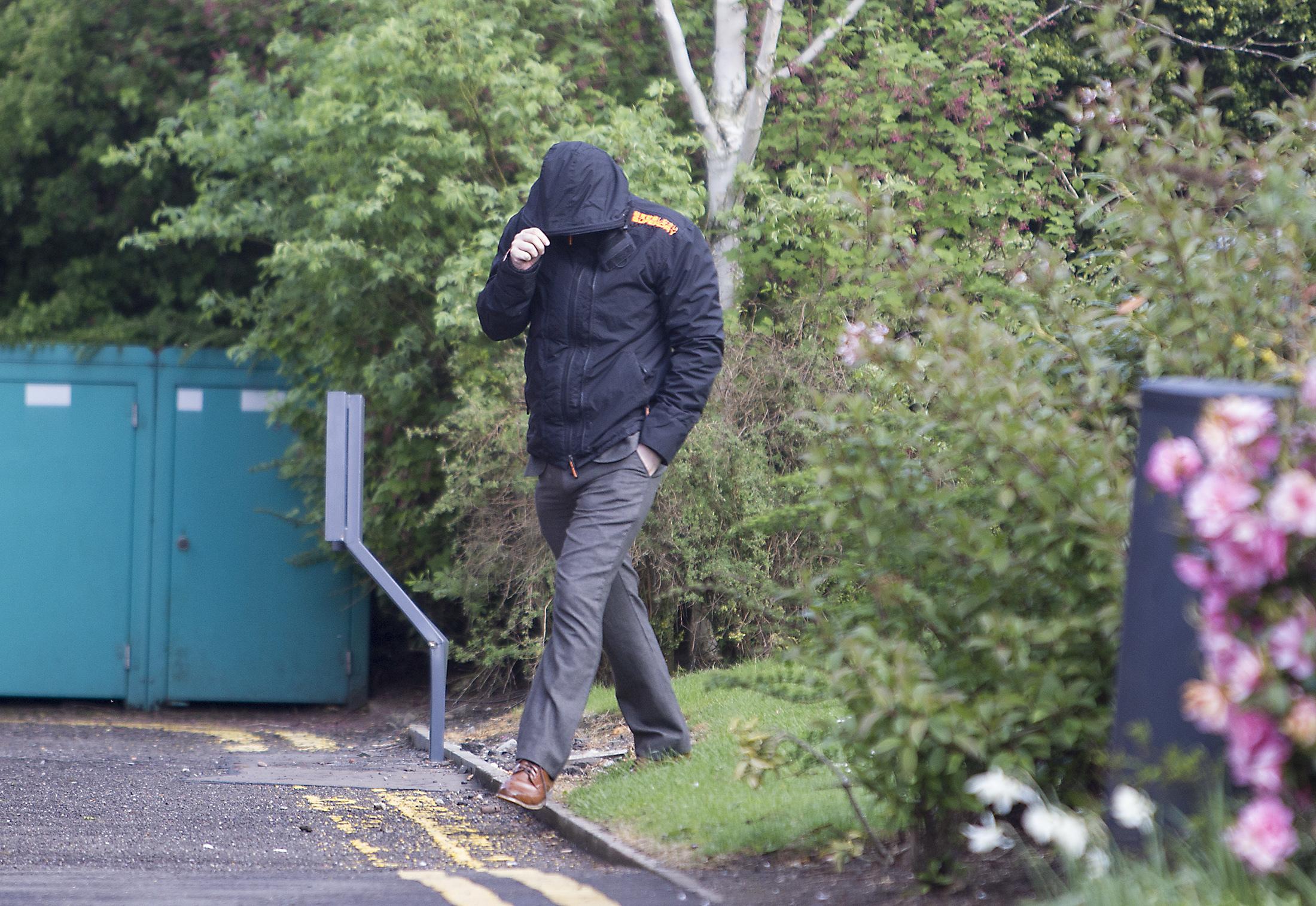 Teacher Stuart Grant covers his face as he arrives at court