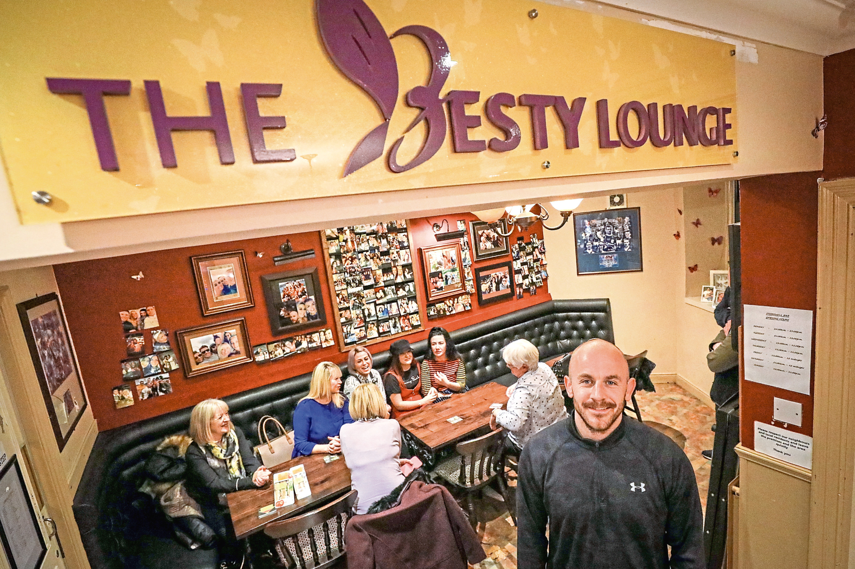 Picture shows Tracey's husband, Greg, in The Besty Lounge which has been decorated with pictures of his wife and many of their friends.