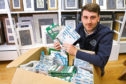 Chris Simpson of the Forfar Photo Centre, with the box of unclaimed photos going back 10 years