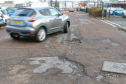 A car avoids the potholes outside Pets at Home