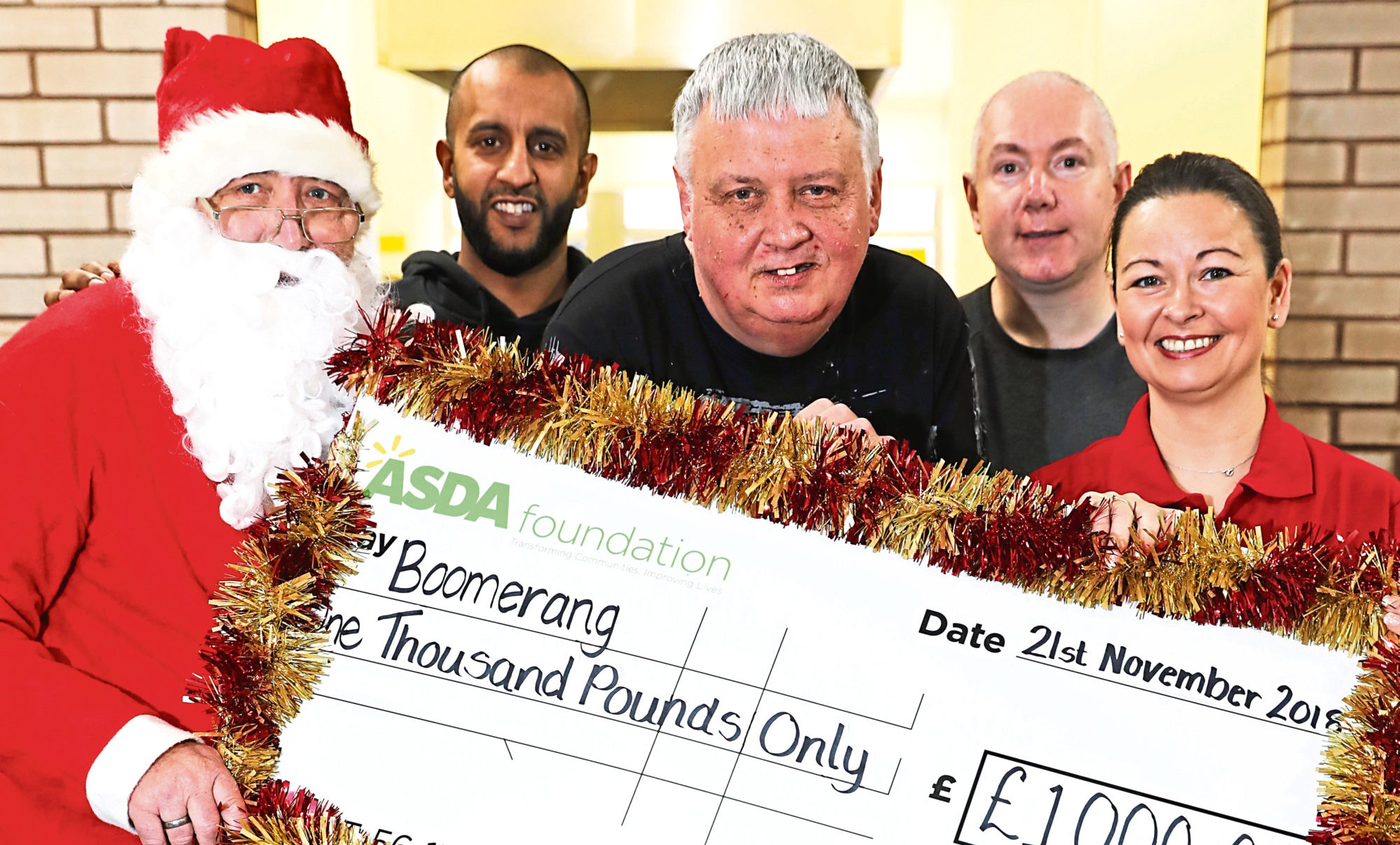Centre manager Neil as Santa, with volunteers Imran Amin, Eddie Gardner and Stewart Mackay with Samantha and the cheque