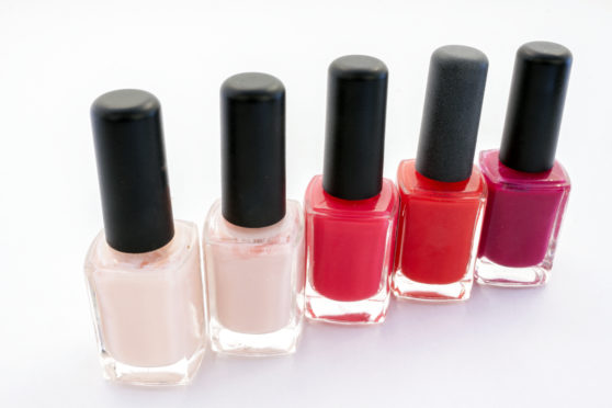 Different bottles of nail polish in different pink and red tones