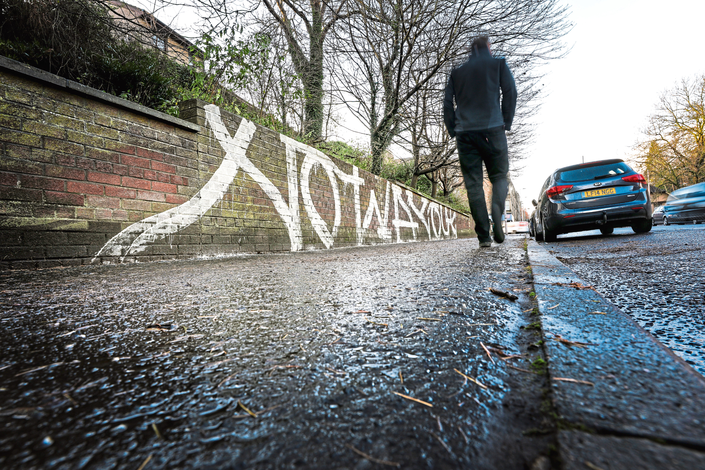 "The ""no way out"" graffiti stretching along the 50-foot wall in Dens Road"