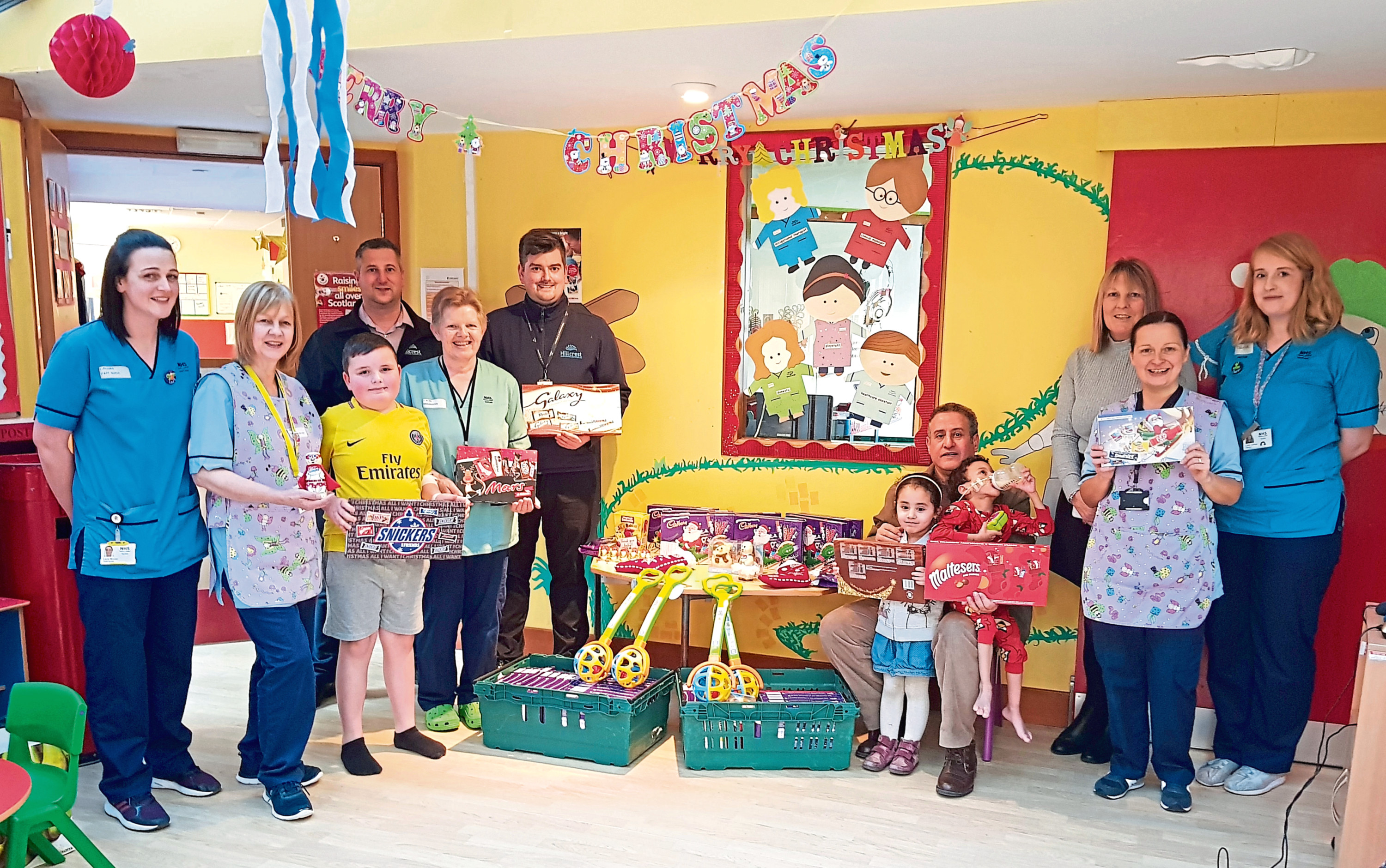 Pictured with the donated goodies which include a range of chocolate selection boxes, are Brian Jones, Steven Maech and Carol Shearer from Hillcrest alongside staff and patients at Tayside Children's Hospital