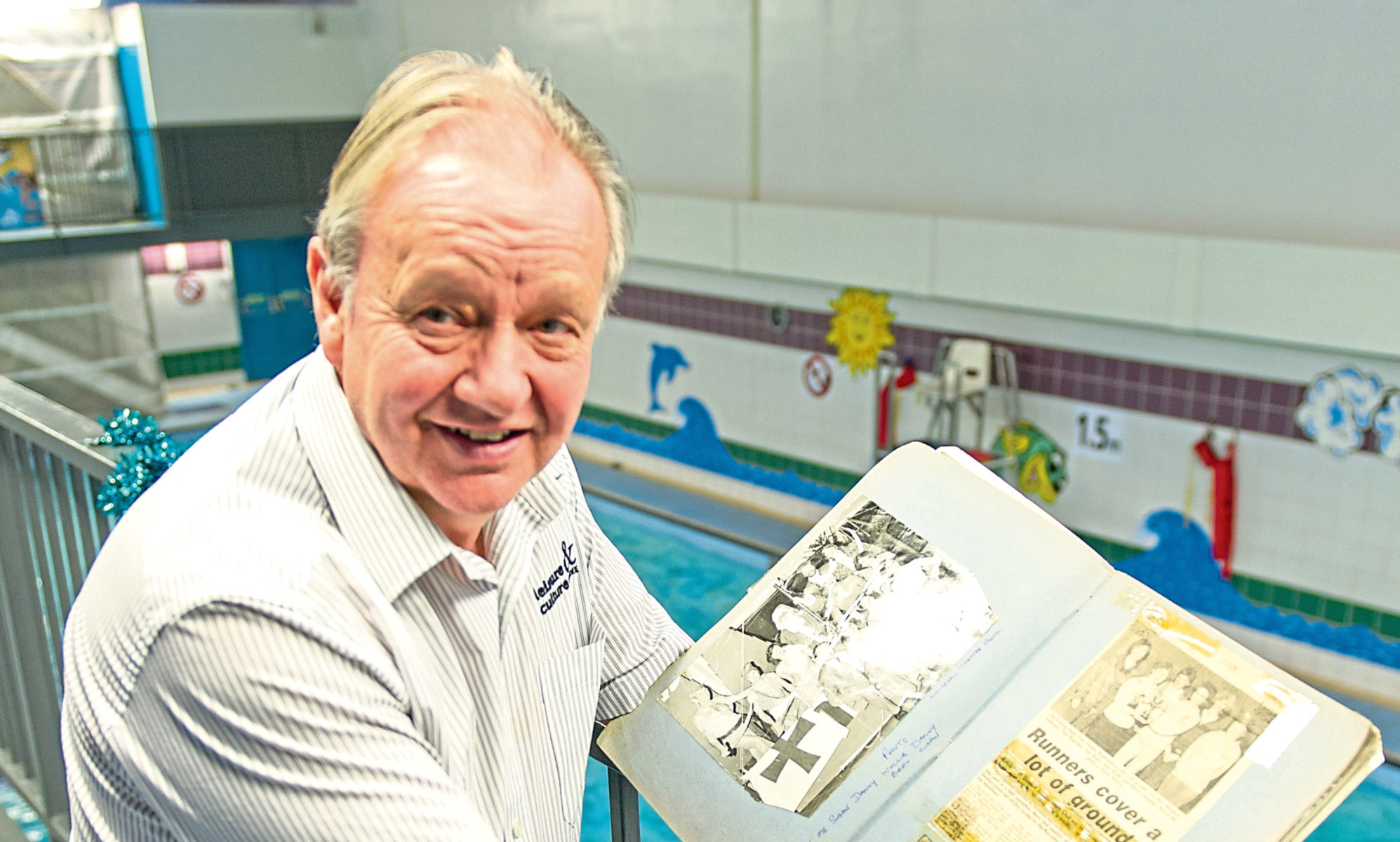 Davie with the scrapbooks, which feature pictures and articles from over the years