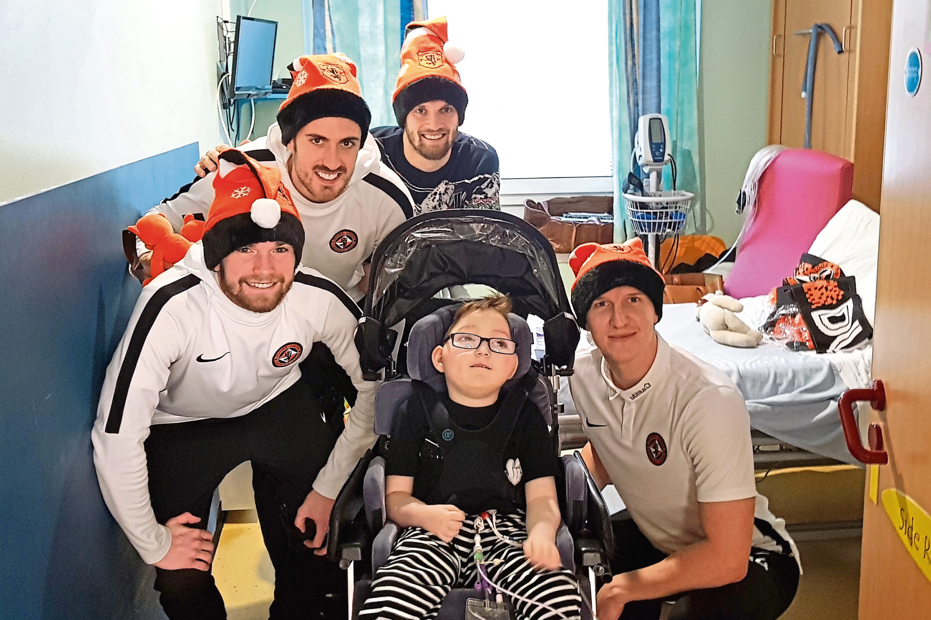 Dundee United players Sam Stanton, Callum Booth, Stewart Murdoch and Paul Watson with young patient Blake McMillan