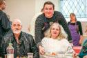 Dean Banks serving up Christmas dinner to Samuel Drummond and Carol Davidson