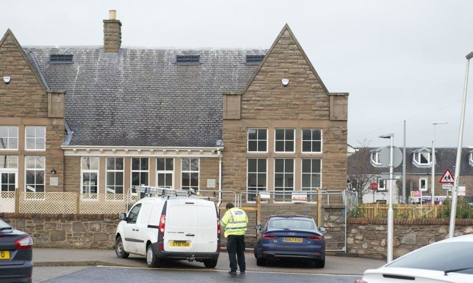 Police inspect the van outside Invergowrie Primary School after the incident