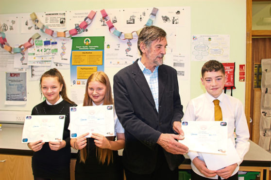 Brian Carroll of the British Science Association awards prizes to Demi Perrie (far left), Joel Campbell and Cerys Rutter