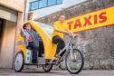 Fleet manager Scott Walker gives Lynne Short a lift in the new rickshaw taxi