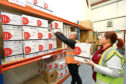 Operations manager Chris Doig and community development worker Amanda O'Connell stacking sanitary products at FareShare Dundee.