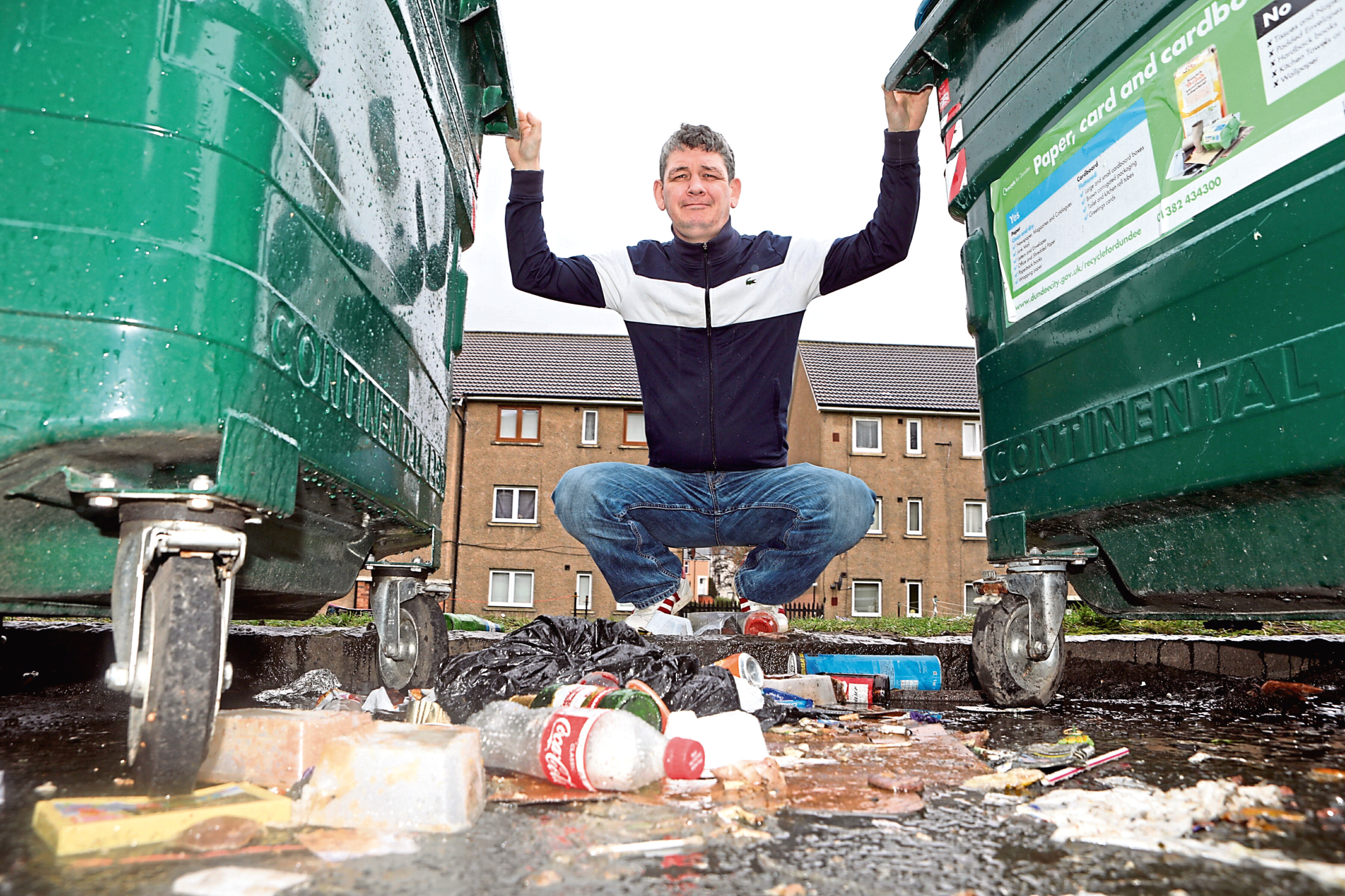 Loganlee Terrace resident Dabid Marr beside the Eurobins in the street