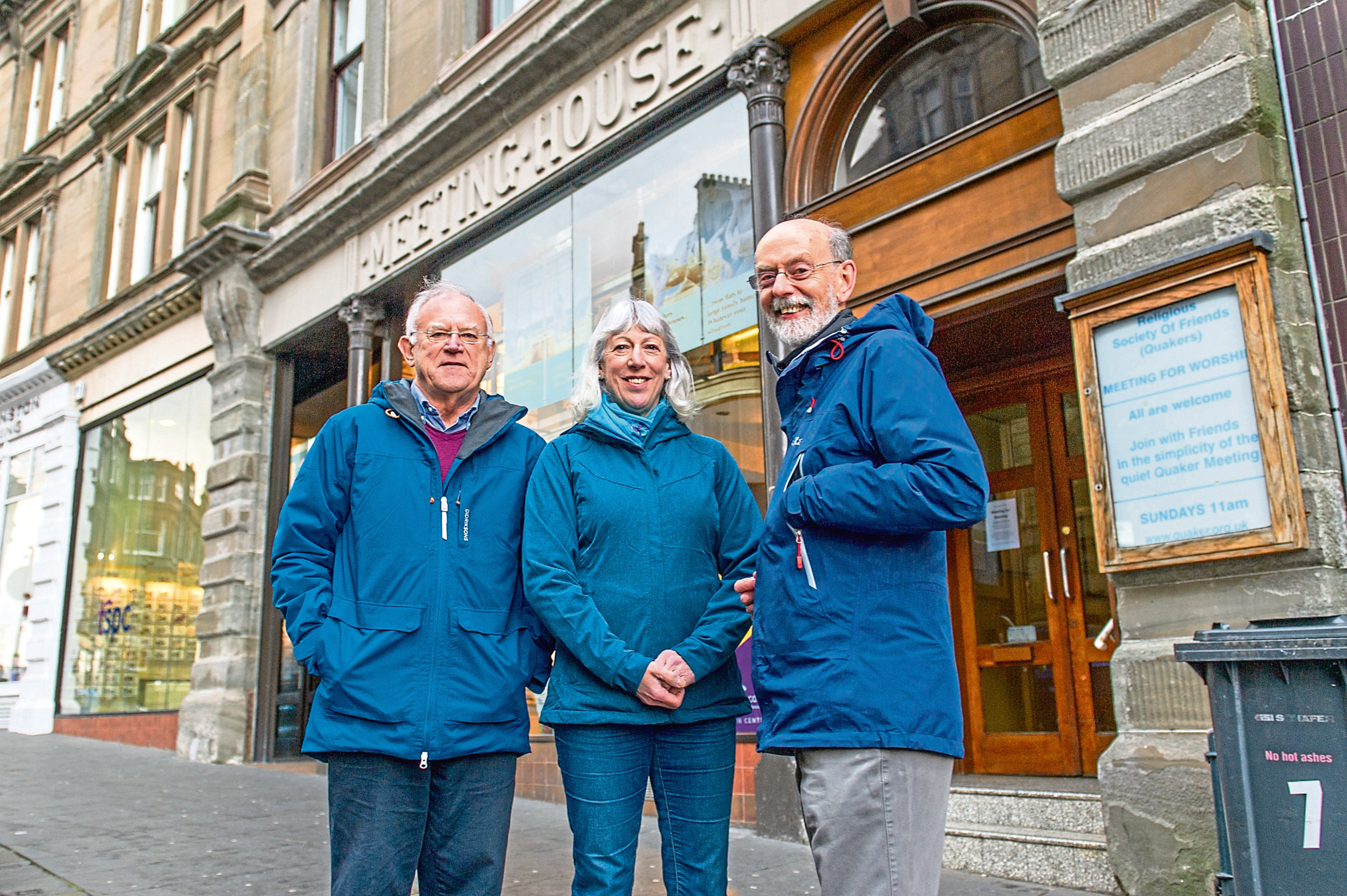 Bill Edgar, Marion Sharkey and Martin Pippard outside the property they hope to move back to. The original sign is carved into the stonework of the building