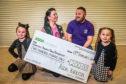 n Picture shows Asda Kirkton community champion Samantha Will presenting the cheque to John alongside pupils Lara Kidd, 7, and five-year-old Alyssa Akkaya.