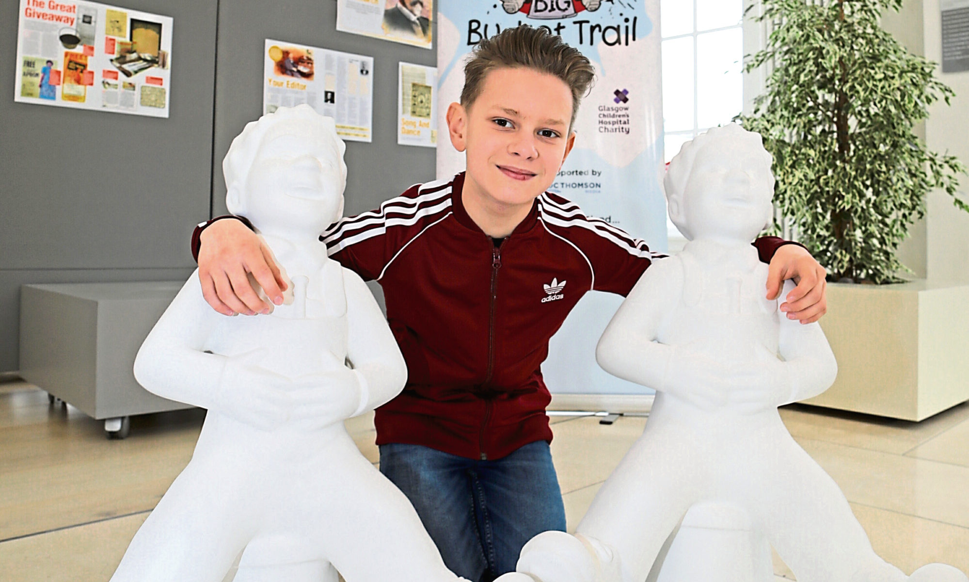 Adam Biesok from Timmergreens Primary School in Arbroath poses with two Wullie statues