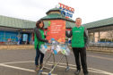 Leon Fields and Indira Mann from Greenpeace return excess plastic to Tesco along with messages from customers